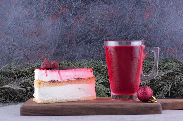 Gâteau au fromage et verre de thé sur planche de bois avec décorations festives. photo de haute qualité