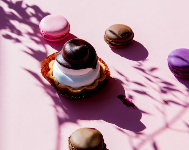 Gâteau au mascarpone et ombres de branche avec des macarons sur une surface rose.