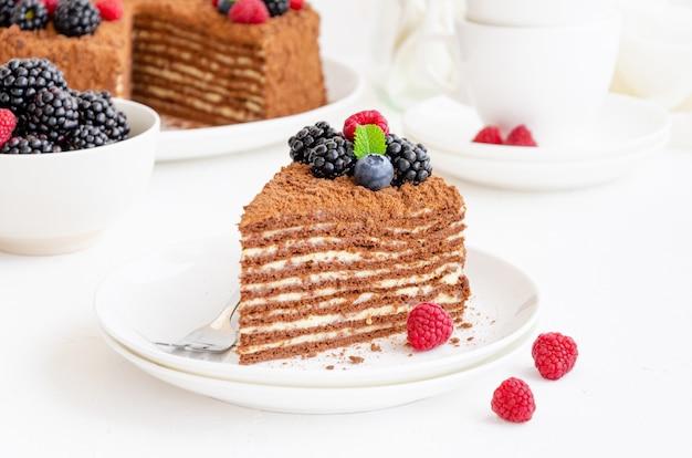 Gâteau au miel au chocolat avec crème et baies fraîches sur une assiette sur fond blanc