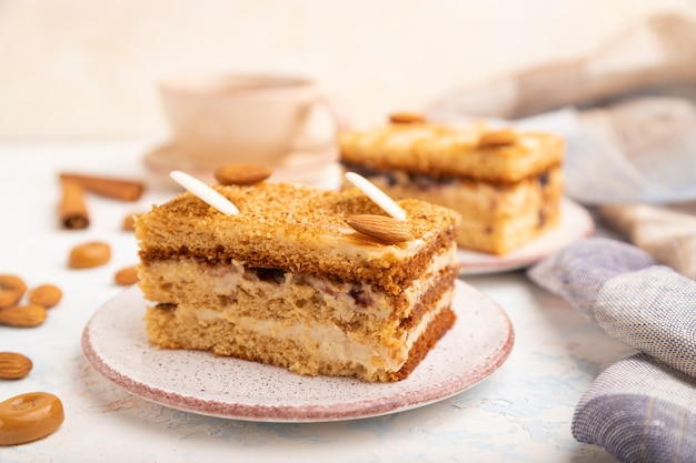 Gâteau au miel avec crème de lait, caramel, amandes et une tasse de café sur fond de béton blanc et textile en lin.