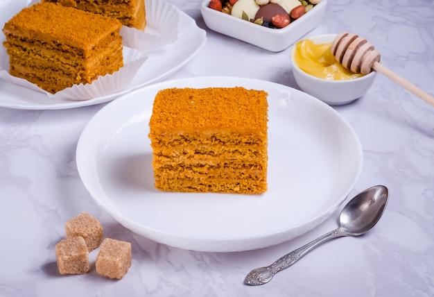 Gâteau au miel avec de la crème sur une plaque blanche sur fond de marbre