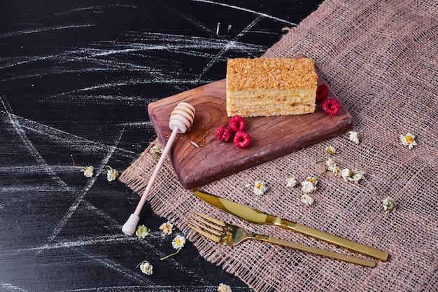 Gâteau au miel avec cuillère au miel et framboises sur fond sombre.