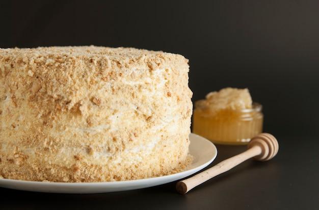 Gâteau au miel fait maison avec de la crème blanche.