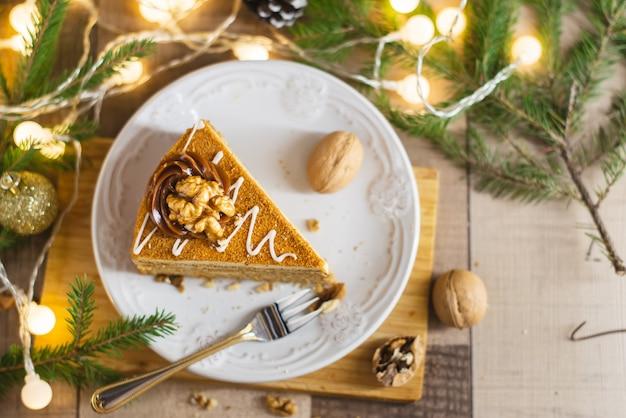 Gâteau au miel fait maison avec de la crème sure sur une table en bois avec des raisins secs et des noix