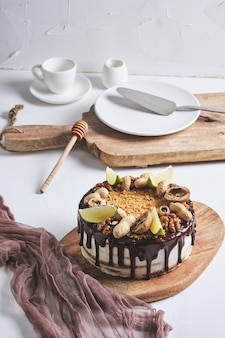 Gâteau au miel maison classique. un gâteau d'anniversaire avec du miel, du chocolat, des noix et du beurre de noix. dessert sur une planche de bois.