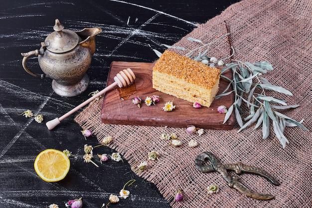Gâteau au miel sur planche de bois avec fleurs séchées et théière.