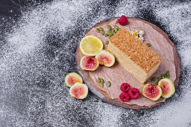 Gâteau au miel sur table noire aux figues et framboises.