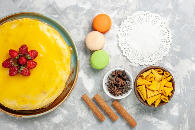 Gâteau au sirop jaune vue de dessus avec des macarons français sur fond blanc