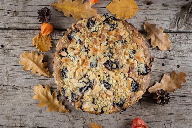 Gâteau automne maison aux noix et prunes sur fond en bois, vue de dessus, espace copie
