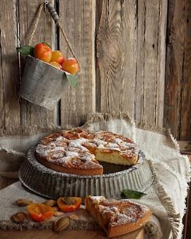 Gâteau aux abricots sur forme vintage sur les vieux murs en bois. seau vintage aux abricots frais