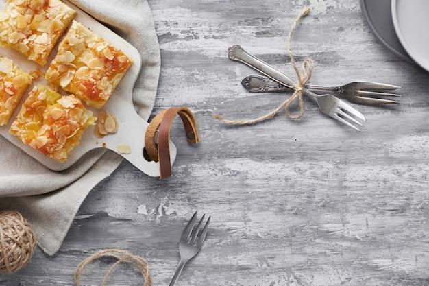 Gâteau aux amandes et thé blac dans une tasse en verre, à plat sur une table texturée grise, espace de texte