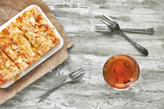Gâteau aux amandes et thé blac dans une tasse en verre, à plat sur une table texturée légère