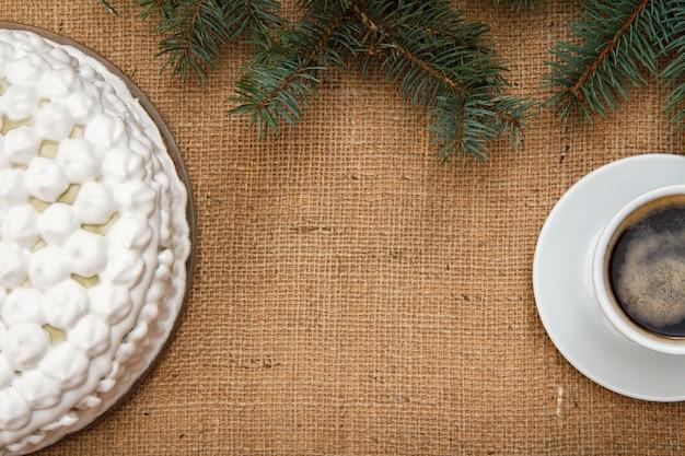 Gâteau aux biscuits décoré de crème fouettée et tasse de café sur table avec branche d'épinette et sac. vue de dessus