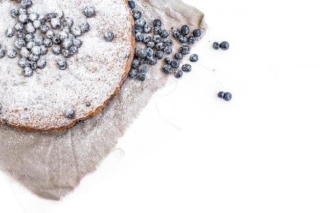 Gâteau aux bleuets avec des bleuets frais et du sucre en poudre sur un tissu beige