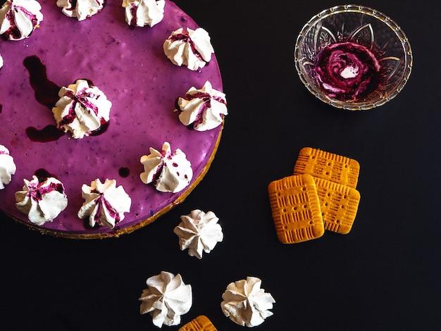 Gâteau aux bleuets avec guimauve sur le dessus et biscuits sur une table sombre
