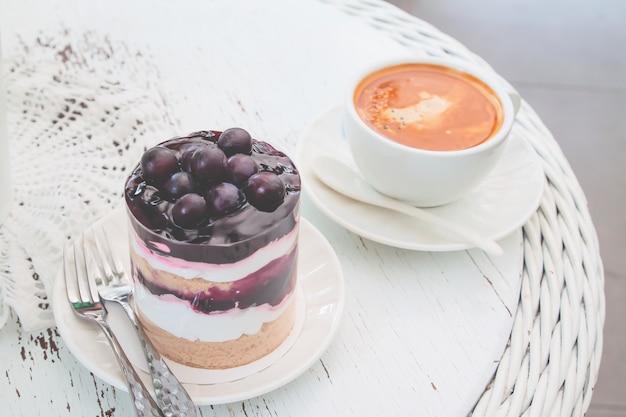 Gâteau aux bleuets avec une tasse d'americano chaud sur la table de style vintage.