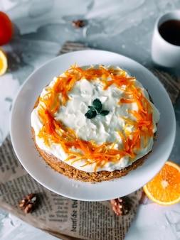 Gâteau aux carottes sur une assiette blanche avec une demi-coupe d'orange et une tasse de café sur fond de marbre clair