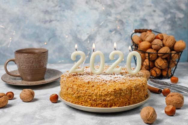 Gâteau aux carottes avec des bougies 2020 et une tasse de thé sur du béton gris
