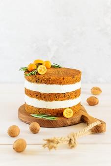 Gâteau aux carottes avec du fromage à la crème sur une planche de bois.