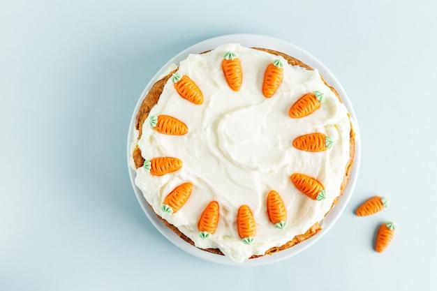 Gâteau aux carottes de pâques avec glaçage sur table bleue