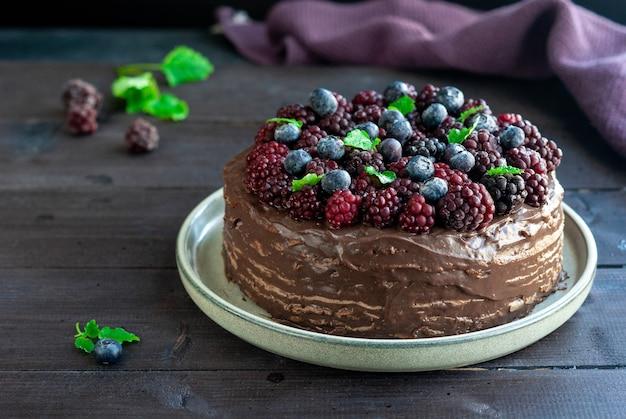 Gâteau aux crêpes au chocolat fait maison avec des baies sur table en bois