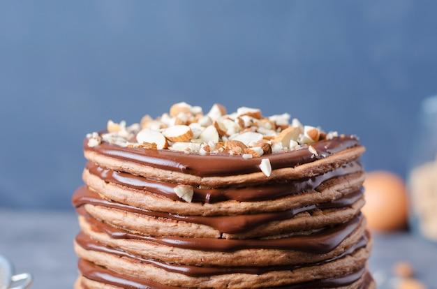 Gâteau aux crêpes. une pile de crêpes au chocolat avec crème au chocolat et amandes.