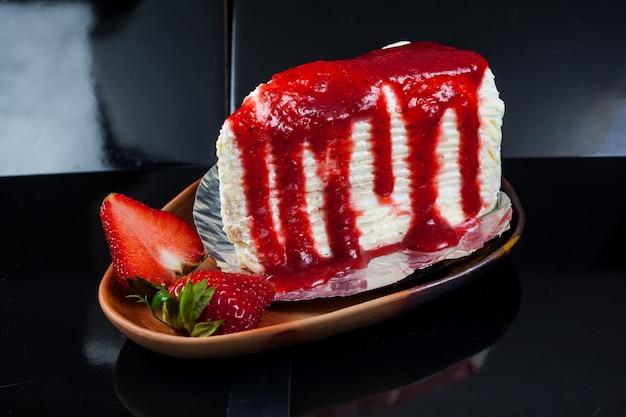 Gâteau aux crêpes avec sauce aux fraises et fraises fraîches.