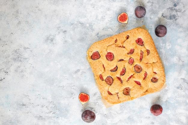Gâteau aux figues avec des figues fraîches sur fond de béton gris.