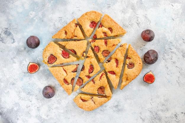 Gâteau aux figues avec des figues fraîches sur une table en béton gris.