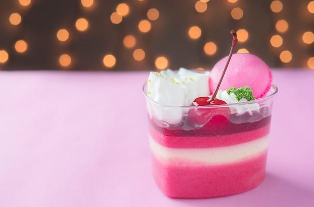 Gâteau aux fraises coloré et macaron sur fond de bokeh brillant
