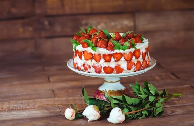 Gâteau aux fraises sur un fond en bois.