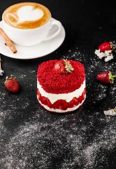 Gâteau aux fraises et tasse de cappuccino sur la table