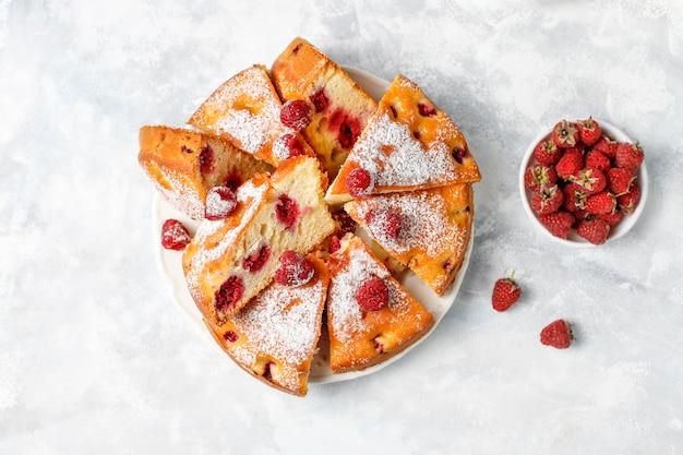 Gâteau aux framboises avec du sucre en poudre et des framboises fraîches à la lumière. dessert aux baies d'été.