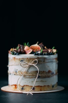 Gâteau aux fruits décoré avec des figues, des biscuits et des myrtilles.
