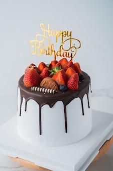 Gâteau aux fruits frais d'anniversaire avec du chocolat joyeux anniversaire sur le concept de gâteau avec un gâteau aux kiwis aux fraises
