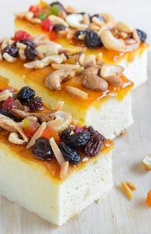 Gâteau aux fruits garni de mélange de fruits et de noix de cajou sur une planche à découper en bois