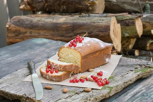 Gâteau aux fruits avec groseille et amande sur une table de jardin