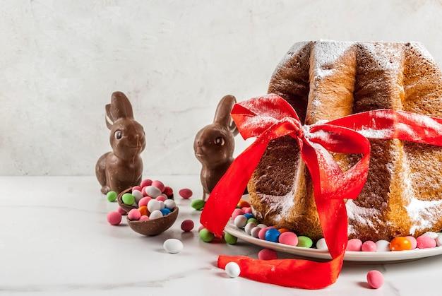 Gâteau aux fruits italien traditionnel panettone pandoro avec ruban rouge festif, lapins de pâques et décorations d'oeufs de bonbons sucrés, sur la maison en bois,
