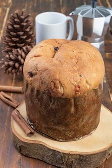 Gâteau aux fruits de noël italien traditionnel panettone sur planche de bois.