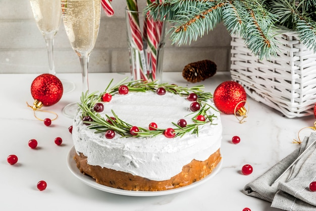 Gâteau aux fruits de noël ou pudding, décoré de romarin et de canneberge, avec décoration de noël, sur table en marbre blanc, espace copie