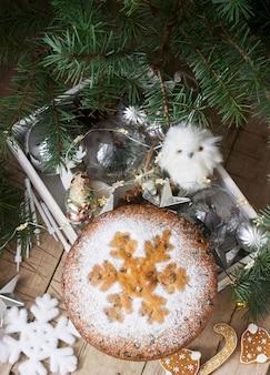Gâteau aux fruits de noël traditionnel sur une boîte avec des jouets de noël et des branches de sapin.