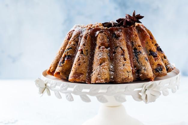Gâteau aux fruits de noël traditionnel, pudding sur plaque blanche