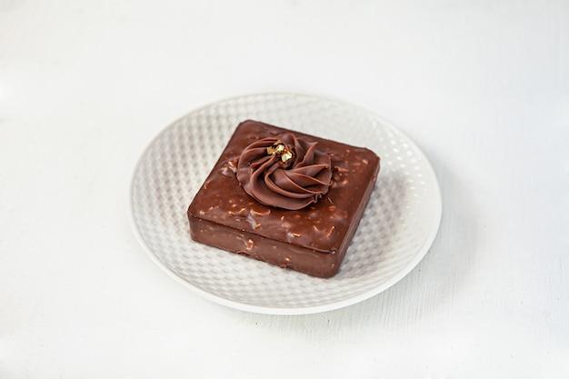 Gâteau aux fruits de la passion et mangue sur le dessus avec une crème ronde sur une assiette blanche ronde