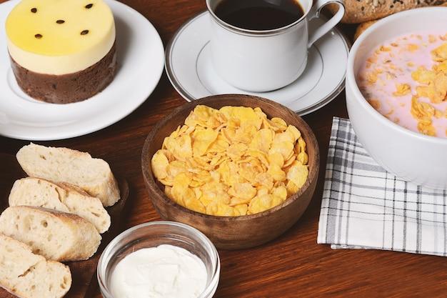 Gâteau aux fruits de la passion, pain grillé, café, yaourt, céréales.