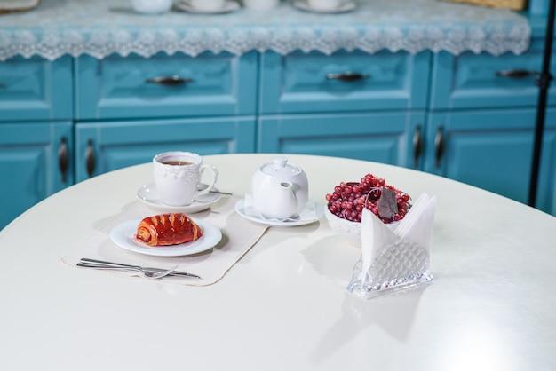 Gâteau aux fruits rouges et thé noir sur la table dans un café confortable
