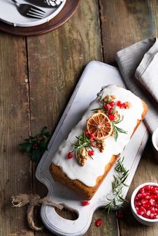 Gâteau aux fruits saupoudré de glaçage, de noix, de noyaux de grenade et de vieux bois orange sec. gateau maison vacances noel et hiver