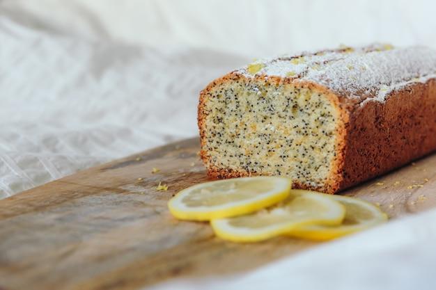 Gâteau aux graines de pavot et au zeste de citron, saupoudré de sucre en poudre. petit gâteau au citron sur une planche de bois.