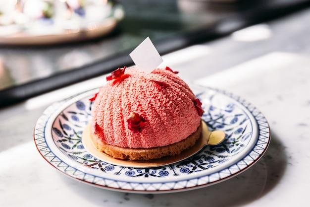 Gâteau aux mousses à la rose et au litchi, décoré de pétales de rose et d'une assiette en chocolat blanc.