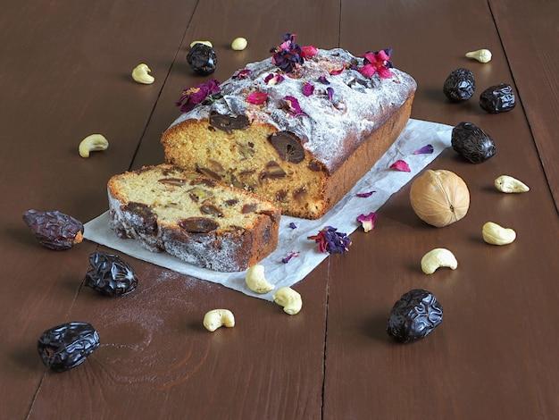 Gâteau aux noix et aux dattes maison sur table en bois