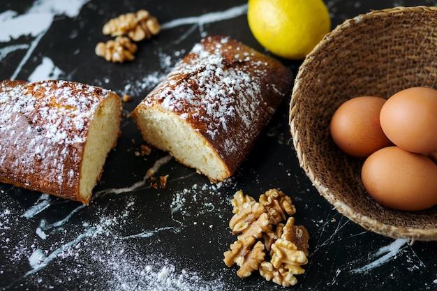 Gâteau aux noix fait maison et ingrédients cuisson concept sur marbre foncé